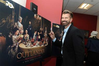 Production designer Jon Gary Steele signs a poster at the Outlander: From Scotland to Paris event, April 5, 2016, at the NYU Skirball Center for the Performing Arts in New York City.