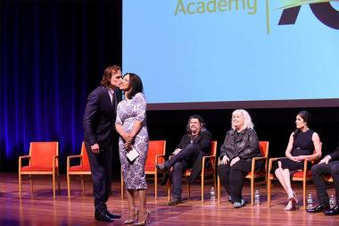 Actor Sam Heughan greets moderator Michelle Miller at the Outlander: From Scotland to Paris event, April 5, 2016, at the NYU Skirball Center for the Performing Arts in New York City.