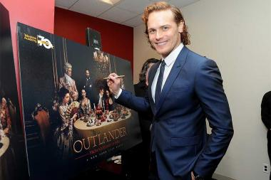 Actor Sam Heughan signs a poster at the Outlander: From Scotland to Paris event, April 5, 2016, at the NYU Skirball Center for the Performing Arts in New York City.