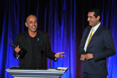 """Editor Jaime Sanchez, right, and Cameraman Jorge Diaz of KVEA Telemundo 52 6pm Newscast accept the award for serious news story – single report for """"Veteranos Desterrados"""" on stage at the Television Academy's 66th Los Angeles Area Emmy Awards"""