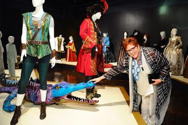Television Academy governor Sue Bub meets a croc from Peter Pan Live! at The 9th Annual Outstanding Art of Television Costume Design Exhibition at the FIDM Museum & Galleries, Saturday, July 18, 2015, in Los Angeles.