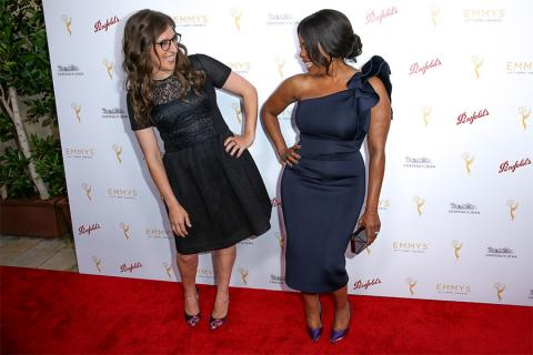 Mayim Bialik and Niecy Nash admire each other's dresses on the red carpet at the Performers Peer Group Celebration August 24 at the Montage in Beverly Hills, California.