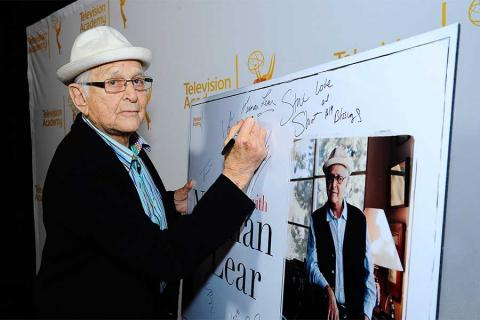 Norman Lear signs the poster at An Evening with Norman Lear at the Montalban Theater in Hollywood.