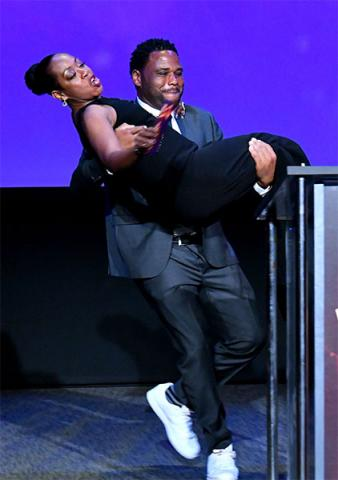Host Anthony Anderson carries presenter Tichina Arnold on stage at the 38th College Television Awards presented by the Television Academy Foundation at the Saban Media Center on Wednesday, May 24, 2017, in the NoHo Arts District in Los Angeles.