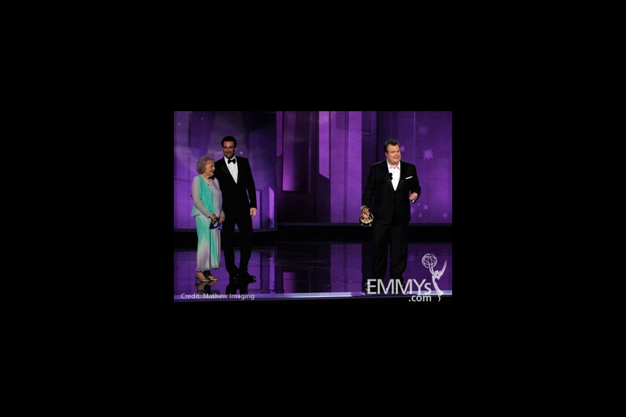 Actor Eric Stonestreet (R) accepts his award from actors Betty White (L) and Jon Hamm onstage at the 62nd Annual Primetime Emmy