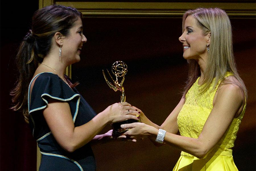 Carolina Cavaliere accepts her award from Lisa Sigell at the 67th Los Angeles Area Emmy Awards July 25, 2015, at the Skirball Cultural Center in Los Angeles, California.
