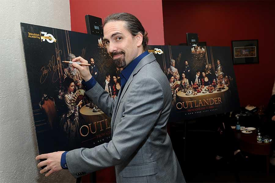 Composer Bear McCreary signs a poster at the Outlander: From Scotland to Paris event, April 5, 2016, at the NYU Skirball Center for the Performing Arts in New York City.