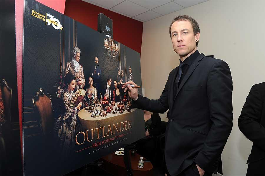Actor Tobias Menzies signs a poster at the Outlander: From Scotland to Paris event, April 5, 2016, at the NYU Skirball Center for the Performing Arts in New York City.