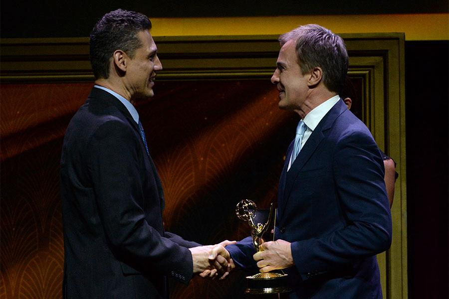 Antonio Camberos accepts his award from Robert Kovacik at the 67th Los Angeles Area Emmy Awards July 25, 2015, at the Skirball Cultural Center in Los Angeles, California.