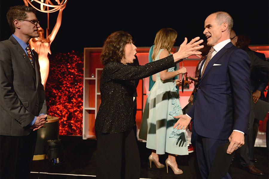 Television Academy governor Lily Tomlin greets Michael Kelly as Television Academy governor Bob Bergen looks on at the Performers Nominee Reception, September 16, 2016 at the Pacific Design Center, West Hollywood, California.