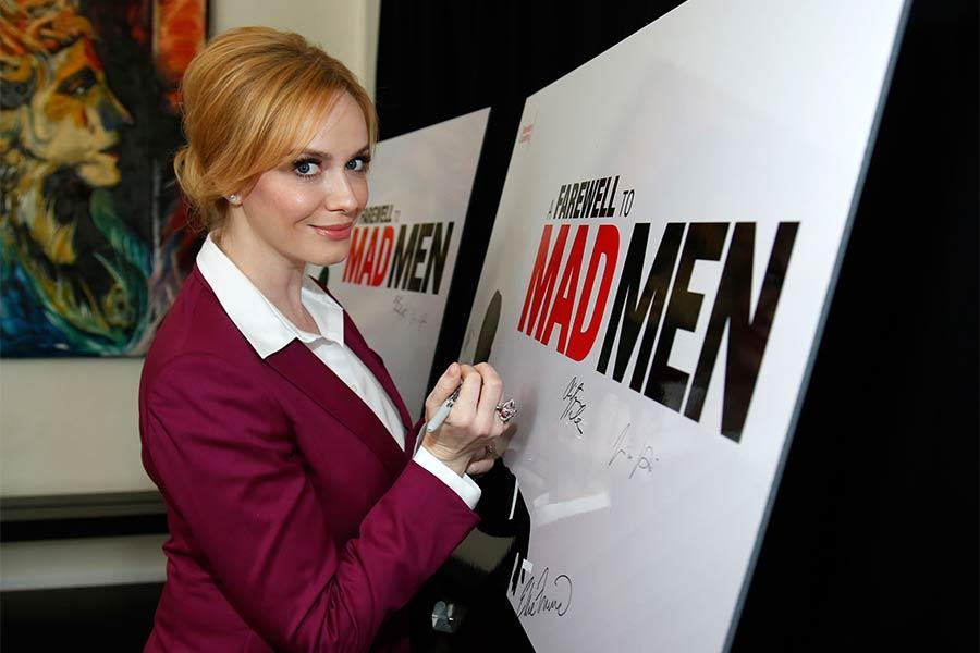 "Christina Hendricks signs the poster at ""A Farewell to Mad Men,"" May 17, 2015 at the Montalbán Theater in Hollywood, California."
