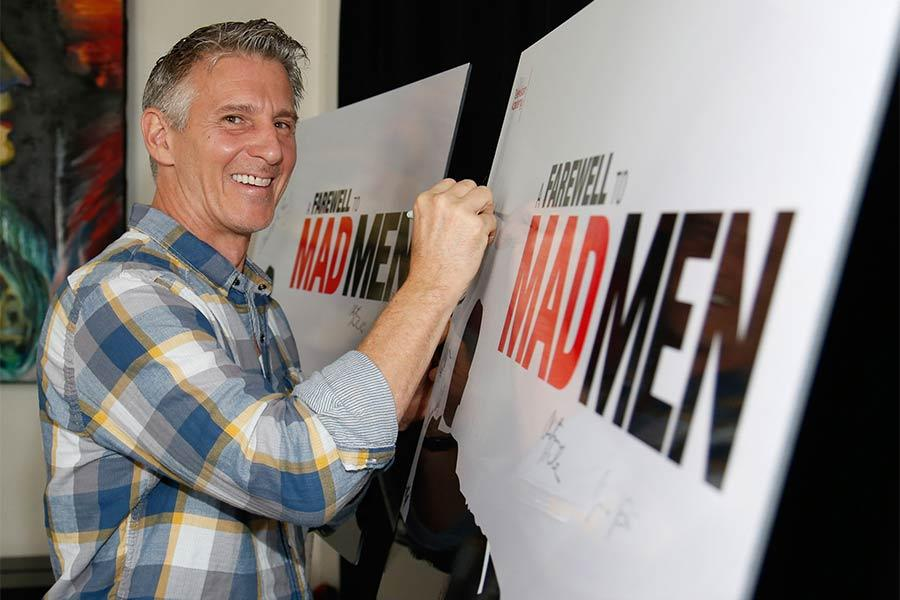 "Christopher Stanley signs the poster at ""A Farewell to Mad Men,"" May 17, 2015 at the Montalbán Theater in Hollywood, California."
