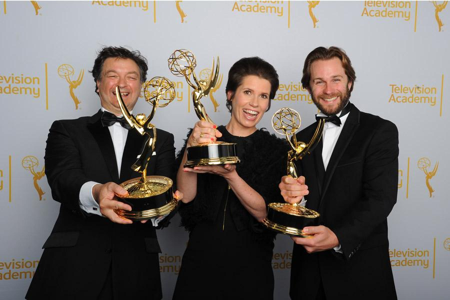 Paul Ghirardani, Deborah Riley and Rob Cameron celebrate their win at the 2014 Primetime Creative Arts Emmys.