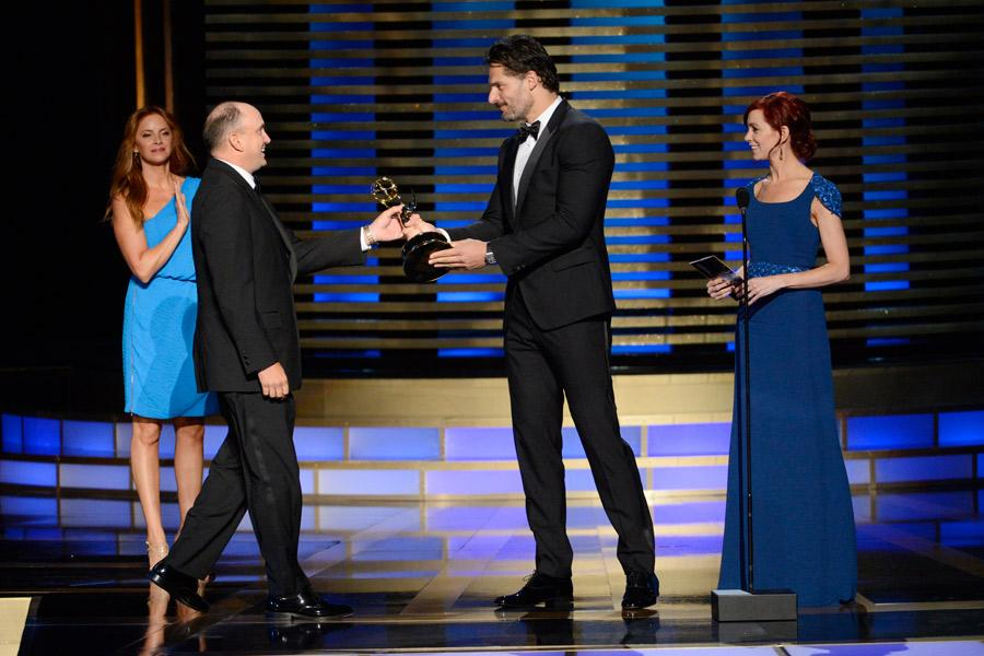 The Blacklist stunt coordinator Cort L. Hessler III (l) accepts an award from Joe Manganiello (c) and Carrie Preston (r) at the 2014 Primetime Creative Arts Emmys.