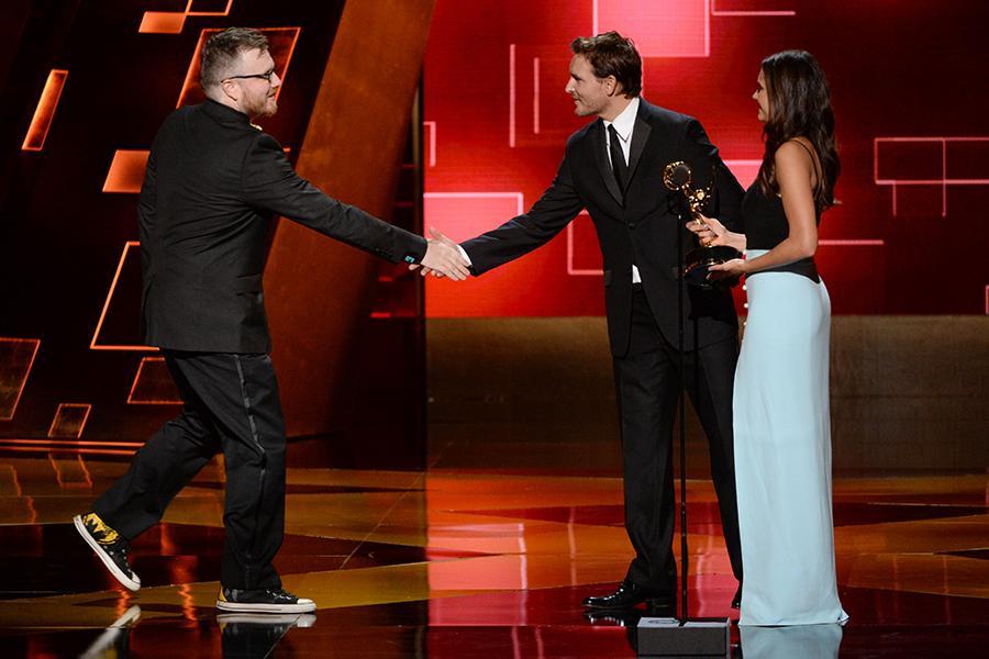 Josh Earl accepts his award from Peter Facinelli and Nina Dobrev at the 2015 Creative Arts Emmys.