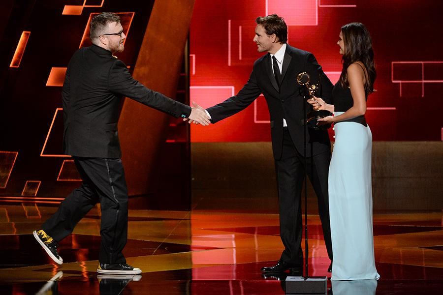 Josh Earl accepts his award from Peter Facinelli and Nina Dobrev at the 2015 Creative Arts Emmys.