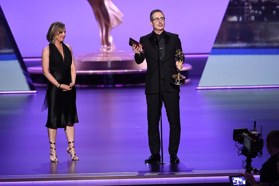 Liz Stanton and John Oliver accept their award at the 71st Emmy Awards.