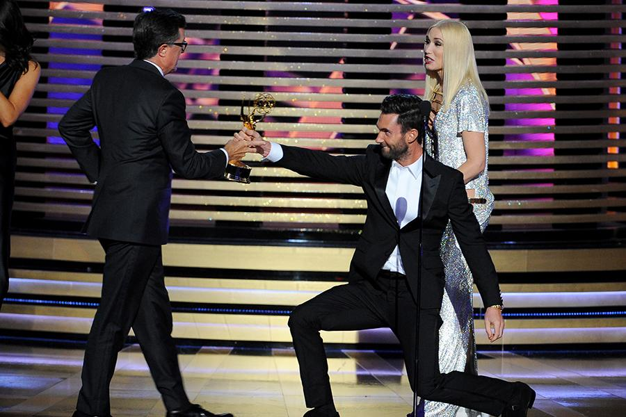 Adam Levine (second from right) of The Voice and Gwen Stefani (r) of The Voice present Stephen Colbert (l) of The Colbert Report an award at the 66th Emmys.