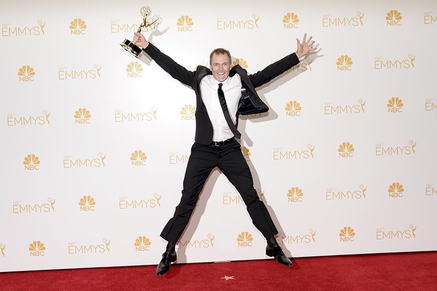 The Amazing Race producer Phil Keoghan celebrates his win at the 66th Emmy Awards.