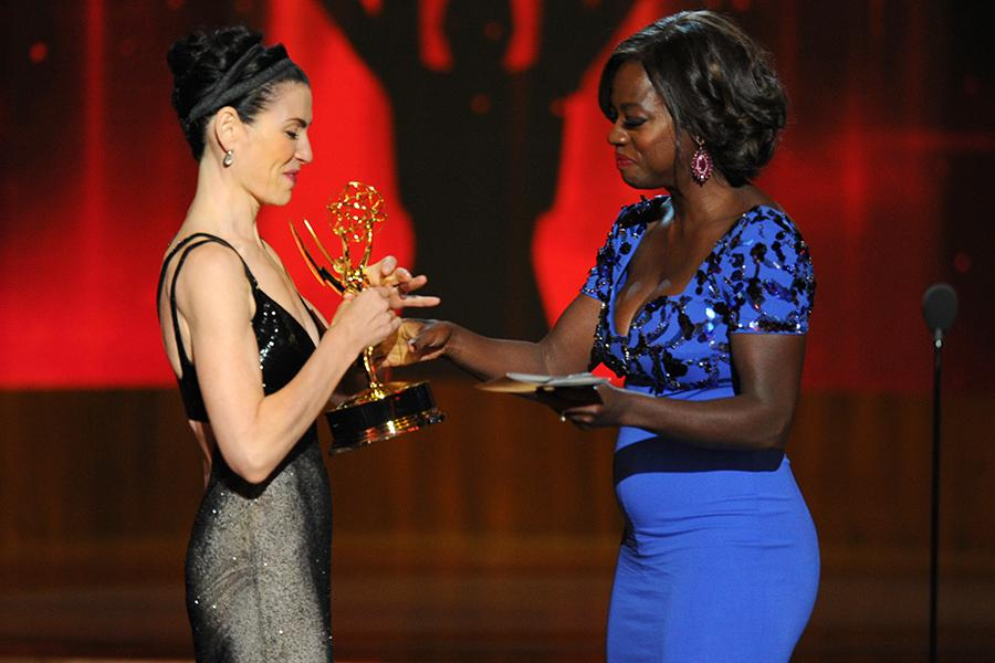 Julianna Margulies (l) of The Good Wife accepts an award from Viola Davis at the 66th Emmy Awards.