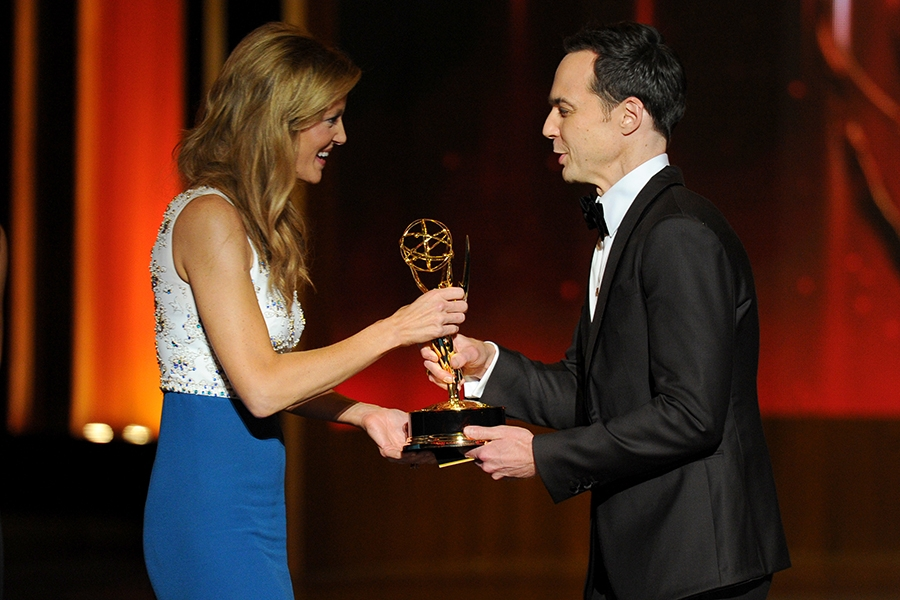 Anna Gunn (l) of Breaking Bad accepts an award from Jim Parsons of The Big Bang Theory at the 66th Emmy Awards.