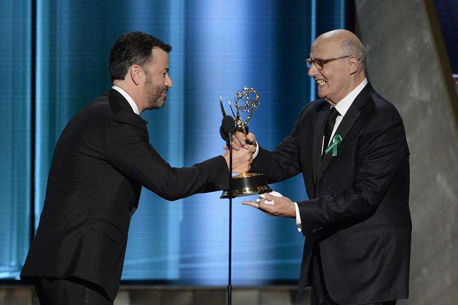 Jimmy Kimmel presents an award to Jeffrey Tambor at the 67th Emmy Awards.