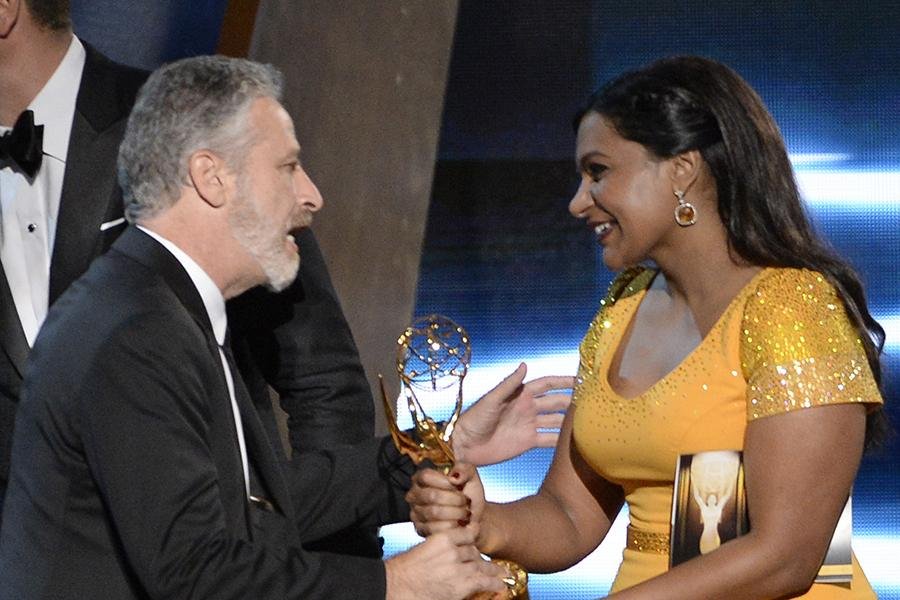 Jon Stewart accepts his award from Mindy Kaling at the 67th Emmy Awards.