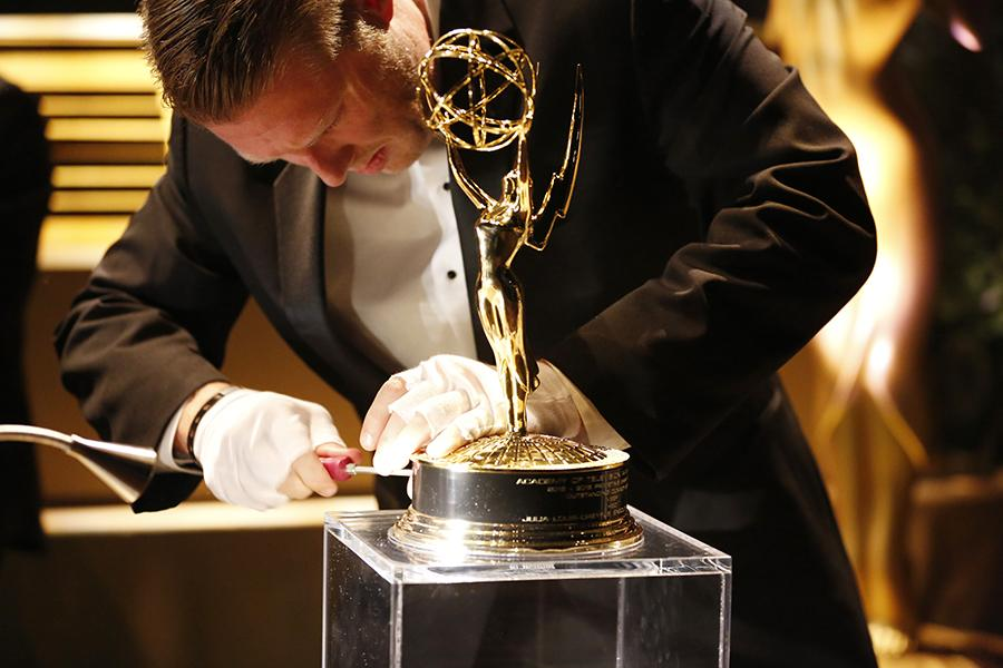 An Emmy statue being engraved at the 68th Emmys Governors Ball.
