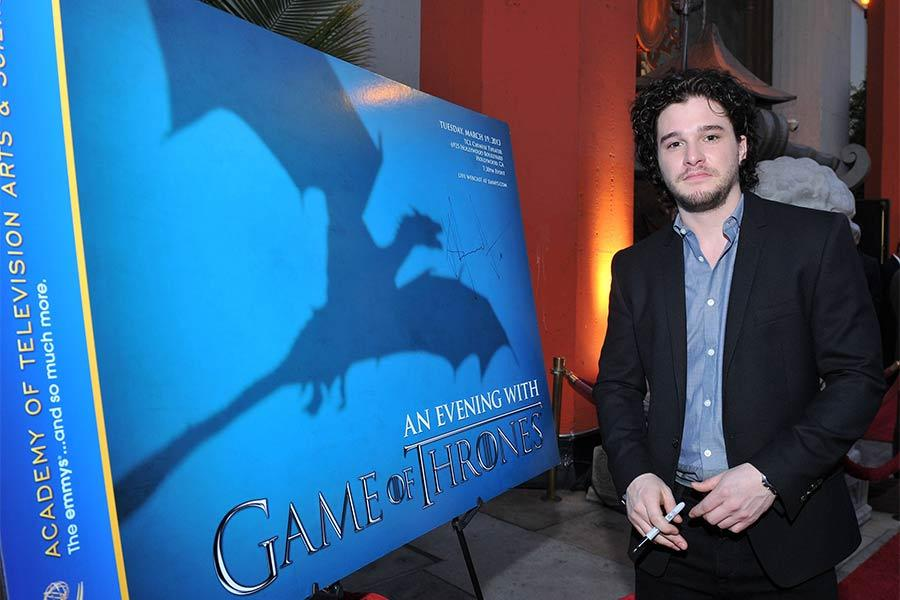 Kit Harrington signs a poster at An Evening with Game of Thrones.
