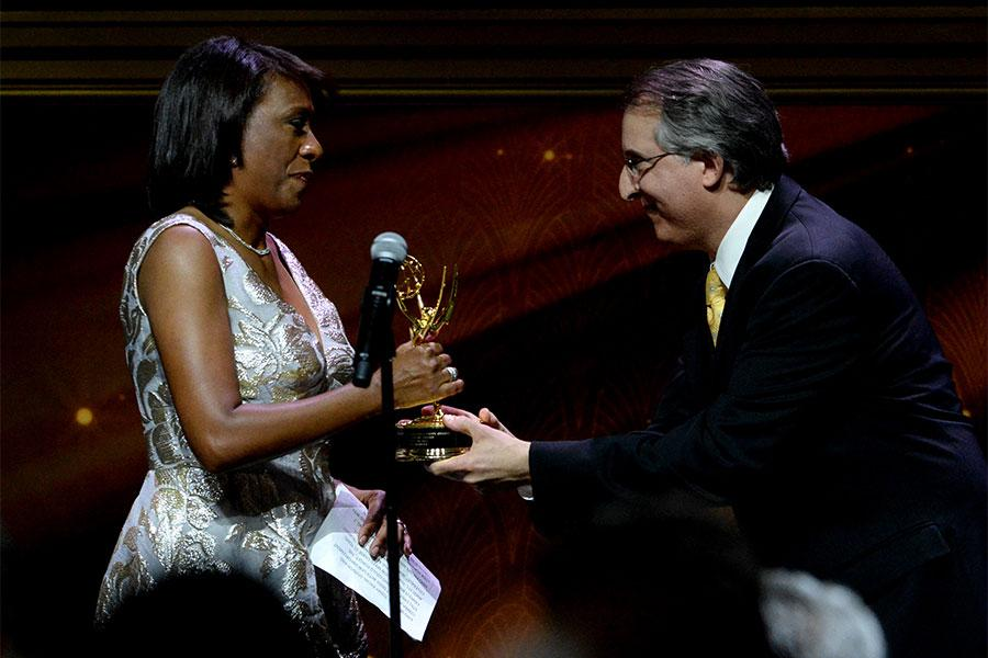 Pat Harvey accepts the Governor's Award from Paul Button at the 67th Los Angeles Area Emmy Awards July 25, 2015, at the Skirball Cultural Center in Los Angeles, California.