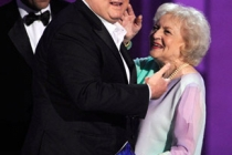 Actor Eric Stonestreet (C) accepts his award from actors Jon Hamm (L) and Betty White onstage at the 62nd Annual Primetime Emmy