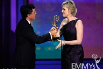 Actress Jane Lynch (R) accepts her award from comedian Stephen Colbert onstage at the 62nd Annual Primetime Emmy Awards held at