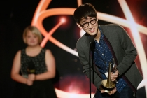 "Hyungjik Lee of Florida State University accepts his award in the Children's Program category for ""Lemonopolis"" at the 35th College Television Awards as presenter Lauren Potter looks on."