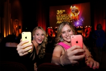 Award nominees Shauna Mackey, left, and Madison Way take selfies in the audience at the 35th College Television Awards