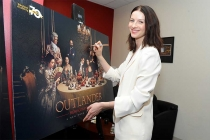 Actor Catriona Balfe signs a poster at the Outlander: From Scotland to Paris event, April 5, 2016, at the NYU Skirball Center for the Performing Arts in New York City.