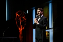 Host Scott Aukerman entertains the audience at the 67th Los Angeles Area Emmy Awards July 25, 2015, at the Skirball Cultural Center in Los Angeles, California.