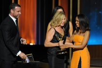 Liev Schreiber (l) and Kerry Washington (r) present an award to Jessica Lange (c) of American Horror Story: Coven at the 66th Emmy Awards.