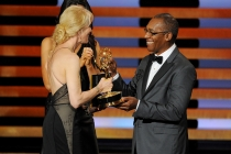 Joe Morton (r) of Scandal presents an award to Breaking Bad writer Moira Walley-Beckett at the 66th Emmy Awards.