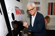 "John Slattery signs the poster at ""A Farewell to Mad Men,"" May 17, 2015 at the Montalbán Theater in Hollywood, California."
