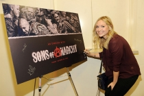 Panel moderator Meg Masters signs the poster at An Evening with Sons of Anarchy.