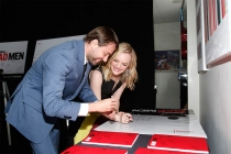 """Actors Vincent Kartheiser and Elisabeth Moss sign posters at """"A Farewell to Mad Men,"""" May 17, 2015 at the Montalbán Theater in Hollywood, California."""